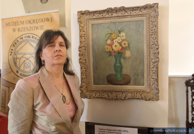 Maria Stopyra, kustosz Muzeum Okręgowego w Rzeszowie przed obrazem Tadeusza Makowskiego