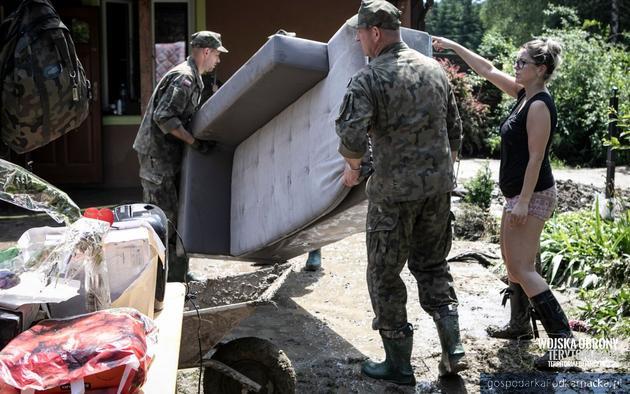 Zołnierze WOT pomagają sprzątać rzeczy po powodzi. Fot. WOT